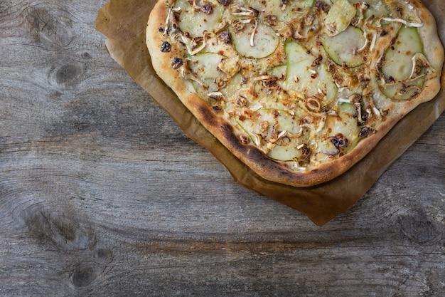 洋ナシ、チーズ、クルミのピザ。ベジタリアンピザのバリエーション。食品の背景