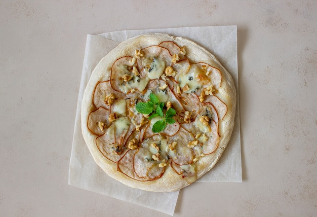 Pizza with pear, gorgonzola cheese, nuts, honey and mint. healthy eating. vegetarian food. recipe.