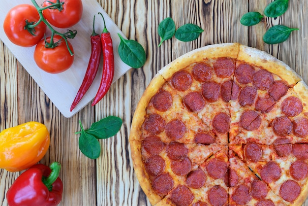 Pizza with pepperoni sausage on a wooden table.