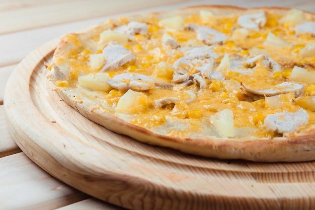 木製のテーブルにパイナップルのピザ