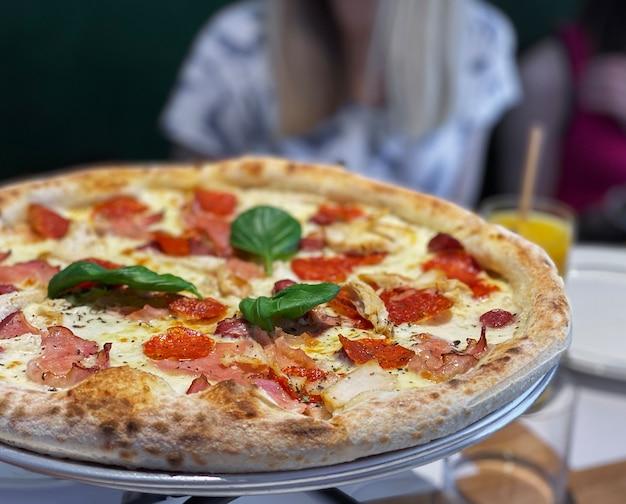 피자 소스, 모짜렐라 치즈, 페퍼로니를 곁들인 피자. 레스토랑에서 테이블에 피자