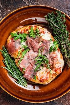 소박한 접시에 프로슈토 파마 햄, 아루굴라 샐러드, 파마산 치즈를 넣은 피자. 나무 배경입니다. 평면도.