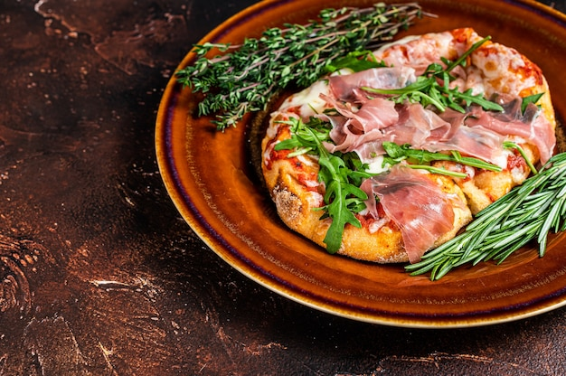 Pizza with prosciutto parma ham, arugula salad and parmesan cheese in a rustic plate. wooden background. top view. copy space.