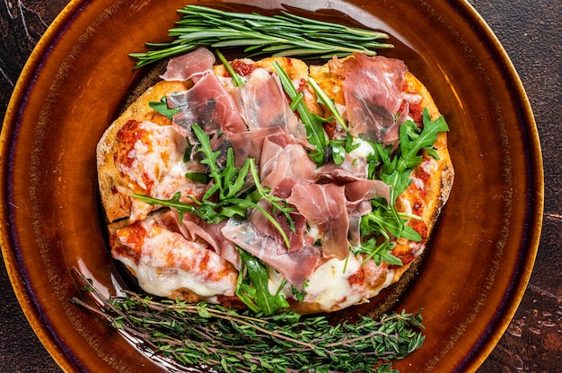 Pizza with prosciutto parma ham, arugula salad and parmesan cheese in a rustic plate. wooden background. top view.