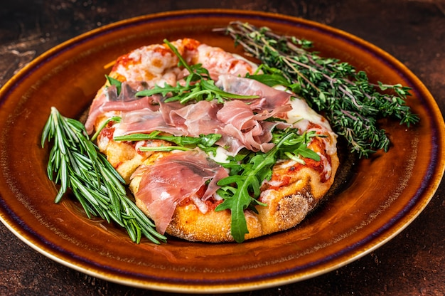 Pizza with prosciutto parma ham, arugula salad and parmesan cheese in a rustic plate