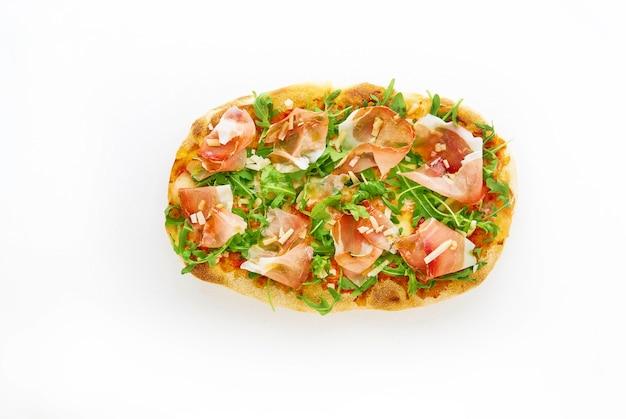 Pizza with prosciutto parma ham arugula salad rocket and parmesan on white