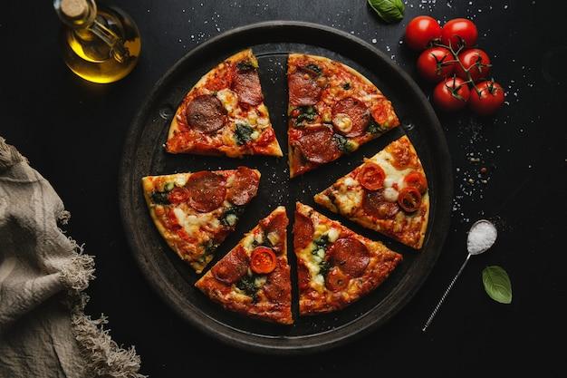 暗い表面にサラミとチーズのピザ