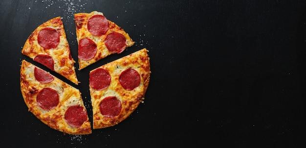 어두운 테이블에 피자 상자에 살라미 소시지와 치즈 피자.