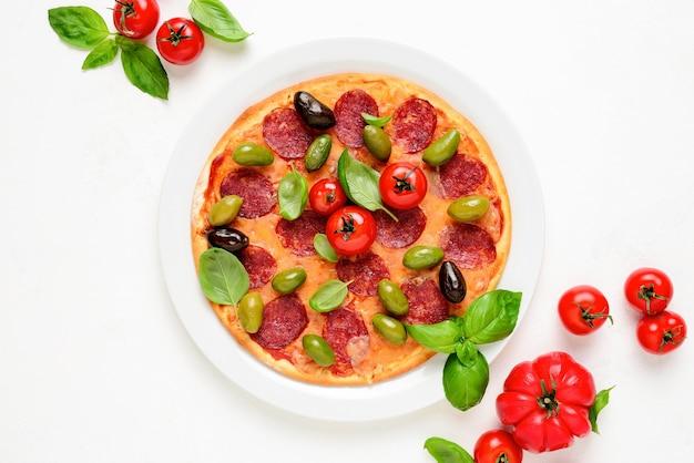 新鮮なバジルの葉で飾られたサラミとオリーブのピザを上から眺める