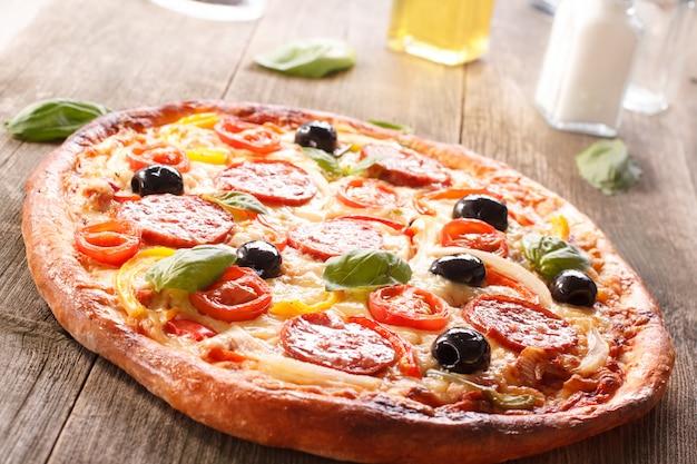 サラミと古い木製の背景に野菜のピザ。