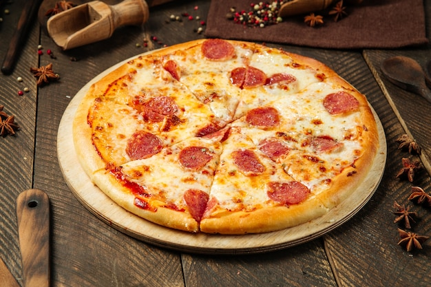 Pizza with salami and cheese on the wooden table