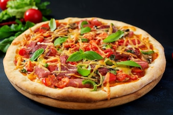 Pizza with salami, ham, tomato, cheese and mushrooms