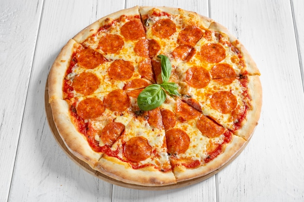 Pizza with salami and mozzarella on white wooden table