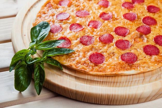 木製のテーブルにサラミのピザ