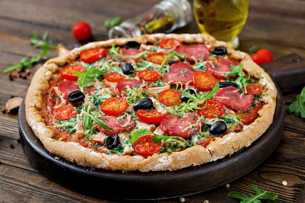 Pizza with salami, tomatoes, olives and cheese on a dough with whole wheat flour. italian food.