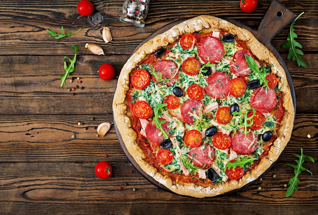 Pizza with salami, tomatoes, olives and cheese on a dough with whole wheat flour.  top vie