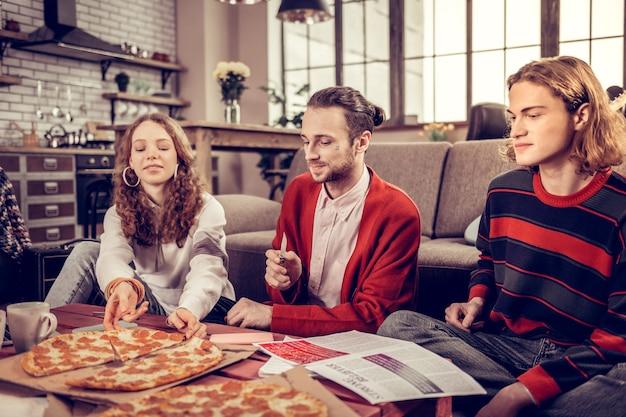 サラミのピザ。ギターを弾いた後、サラミと一緒にピザを食べながら幸せを感じる2人の兄弟姉妹