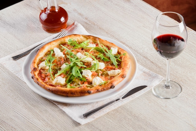 Pizza with salmon, feta cheese, sauce, tomatoes, on white round plate on light wooden table on background of glass of red wine