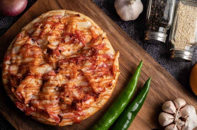 Пицца с колбасой, кукурузой, фасолью, креветками и беконом на деревянной тарелке