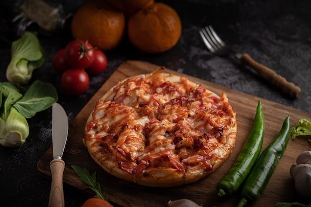Pizza con salsiccia, mais, fagioli, gamberetti e pancetta su un piatto di legno