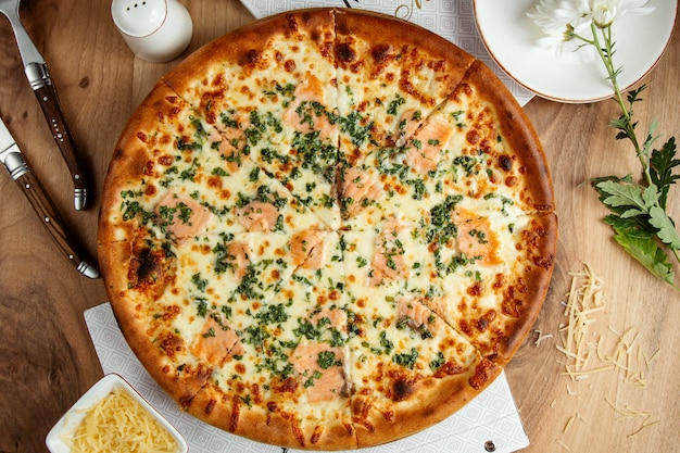 ソーセージグリーンとパルメザンチーズのトップビューのピザ