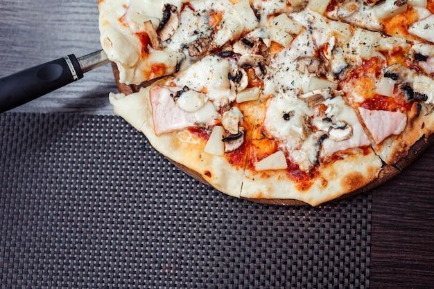 Пицца с сосисками, грибами и моцареллой. вид сверху. лопатка, поднимающая кусок пиццы. свободное место для вашего текста.