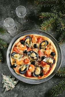 Пицца с мидиями из морепродуктов в ракушках, хвостами креветок, каперсами и оливками