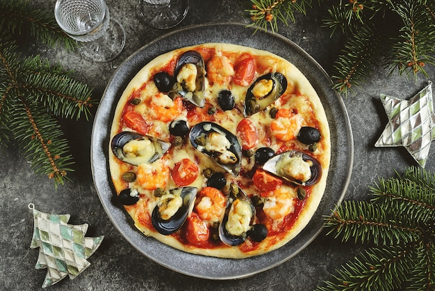 Pizza with seafood mussels in shells, shrimp tails, capers and olives
