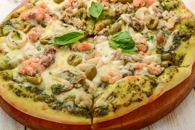 Pizza with shrimp, salmon and olives, pesto