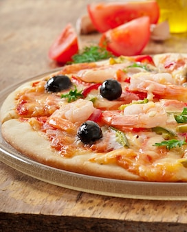 Pizza with shrimp, salmonnd olives