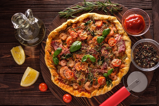 Pizza with shrimps, tomatoes, cheese and herbs on a wooden background