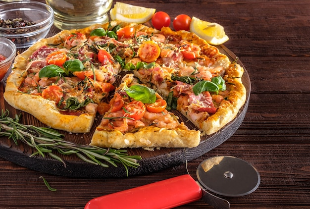 Pizza with shrimps, tomatoes, cheese and herbs