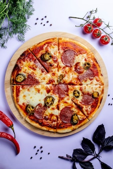 Pizza with side vegetables and herbs