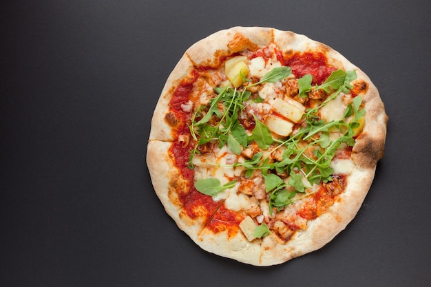 Pizza with smoked ham and rucola on black background. tasty thin italian pizza with meat on dark ground-top view flat lay