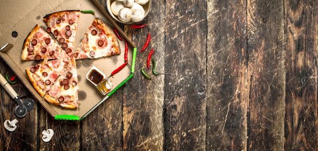 매운 고기 소시지와 치즈 피자. 나무 배경에