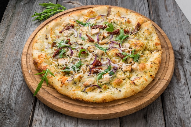 Pizza with sun-dried tomatoes, prosciutto, arugula and parmesan cheese