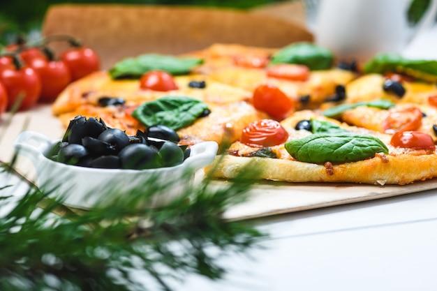 Пицца с помидорами и шпинатом на белом фоне и рождественские еловые ветки