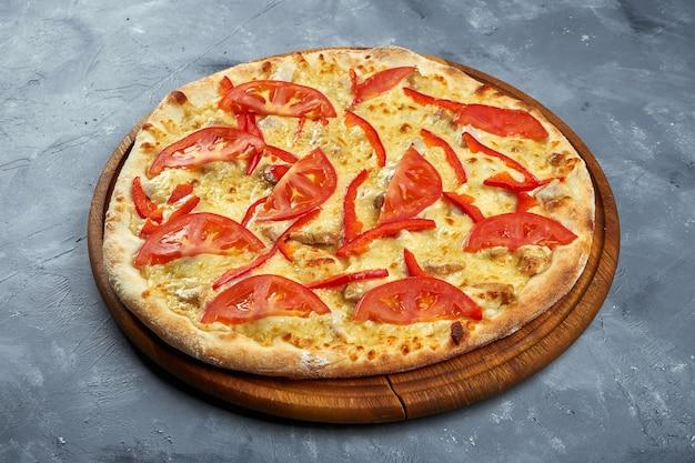 木製トレイにトマト、ピーマン、チキン、チーズのピザ