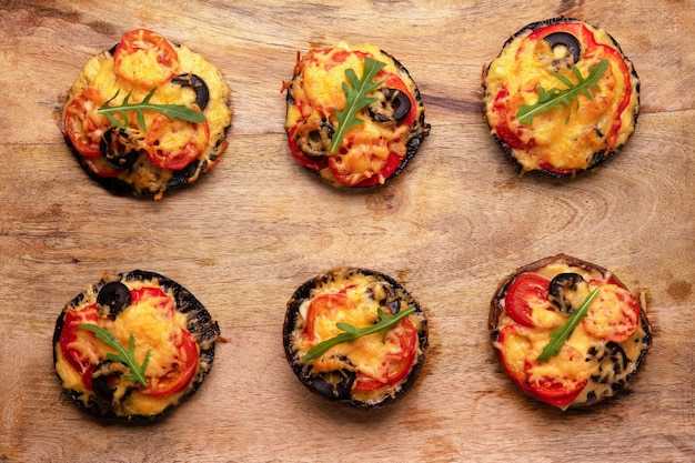 Pizza with tomatoes, cheese and pepper on portobello mushrooms, top view with delicious food