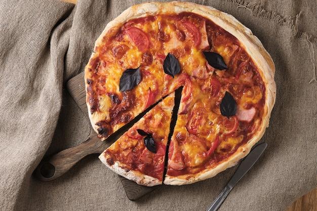 Пицца с помидорами, моцареллой, томатным соусом и копченостями. вкусная домашняя пицца. вкусная итальянская кухня.