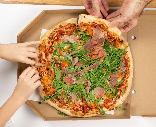 Пицца с помидорами, прошутто, рукколой и моцареллой
