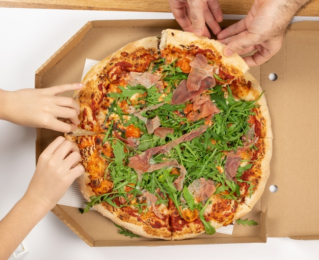 Pizza with tomatoes, prosciutto, arugula and mozzarella