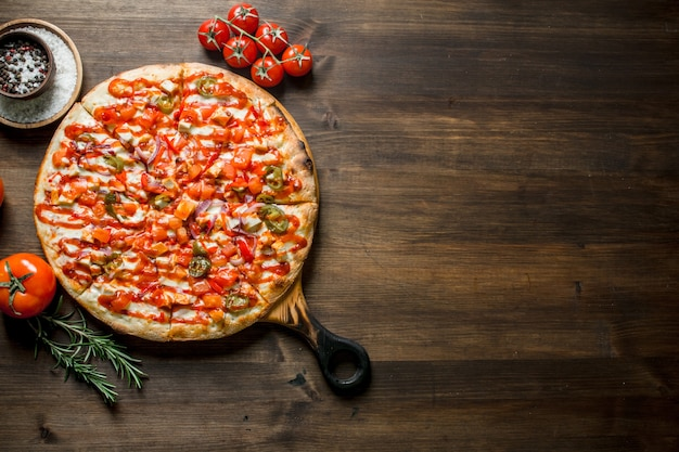 Pizza with tomatoes and rosemary on rustic table