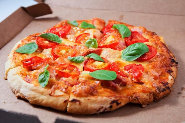 골판지 상자에 토마토, 소시지, 치즈를 넣은 피자