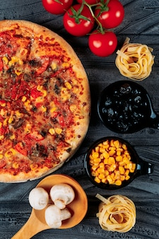 Pizza with tomatoes, spaghetti, corn, olives, mushrooms close-up on a dark background