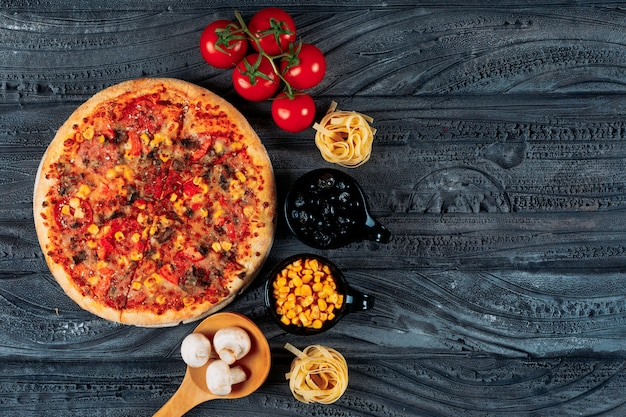 Pizza with tomatoes, spaghetti, corn, olives, mushrooms top view on a dark blue background