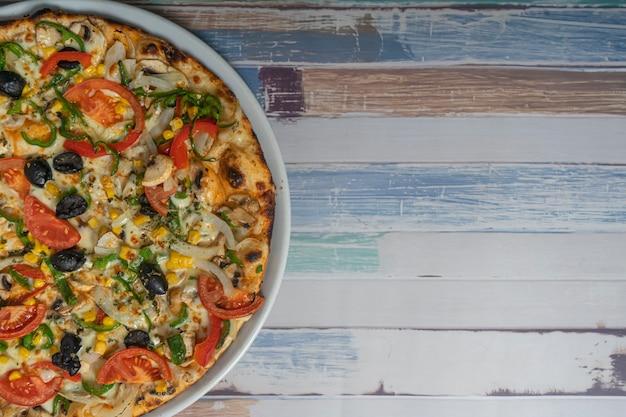 木製のテーブル、コピースペースに野菜の食材を使ったピザ