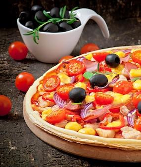 野菜、鶏肉、ハム、白で隔離されるオリーブのピザ