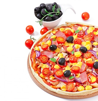 Pizza with vegetables, chicken, ham and olives isolated on white