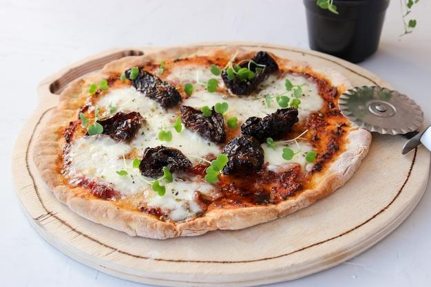 Pizza on a wooden board with mozzarella, mini arugula.